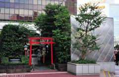 Tradition and modernity, small shrine surrounded by skyscrapers
